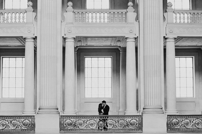 san francisco city hall engagement photo of puja & john kissing