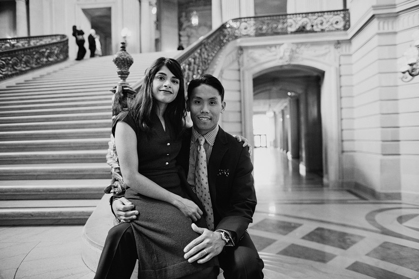 san francisco city hall engagement photo of puja sitting in john's lap