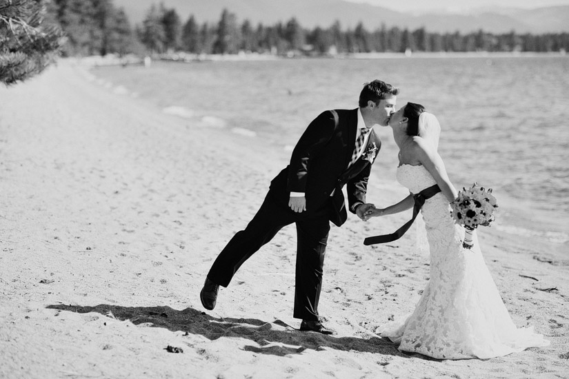 edgewood wedding photo of andrea and joe kissing on the shores of lake tahoe