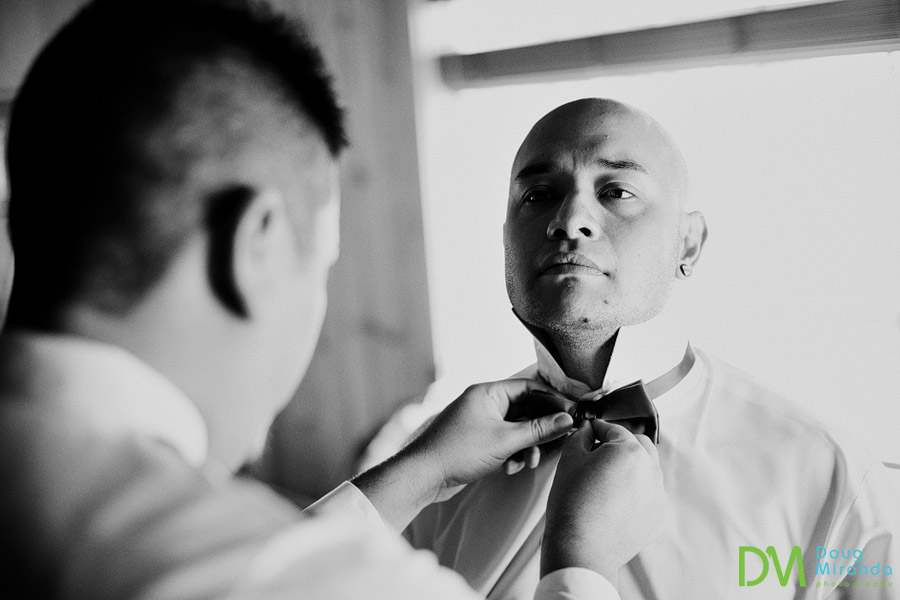 one of james's groomsmen helping him put on his bow tie before his zephyr cove wedding