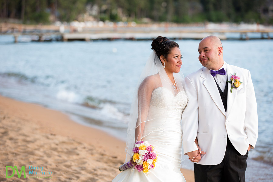 a wedding couple walking together on the shores of zephyr cove