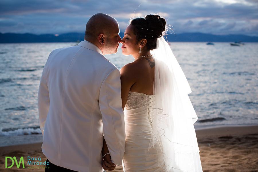 a wedding couple cuddling at sunset on lake tahoe