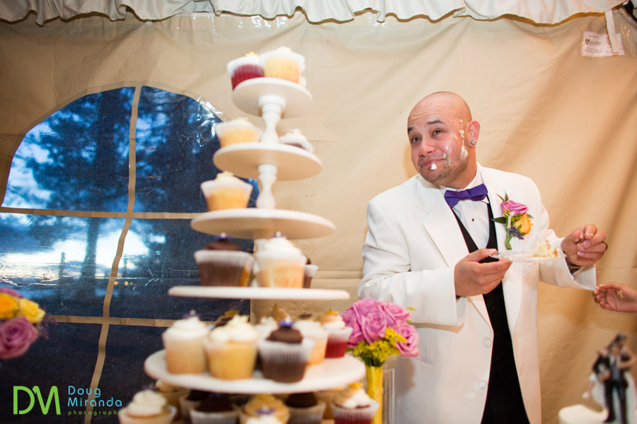 a groom with smashed wedding cake on his face