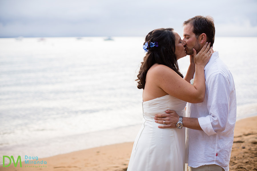 angela and george kissing during their beach wedding