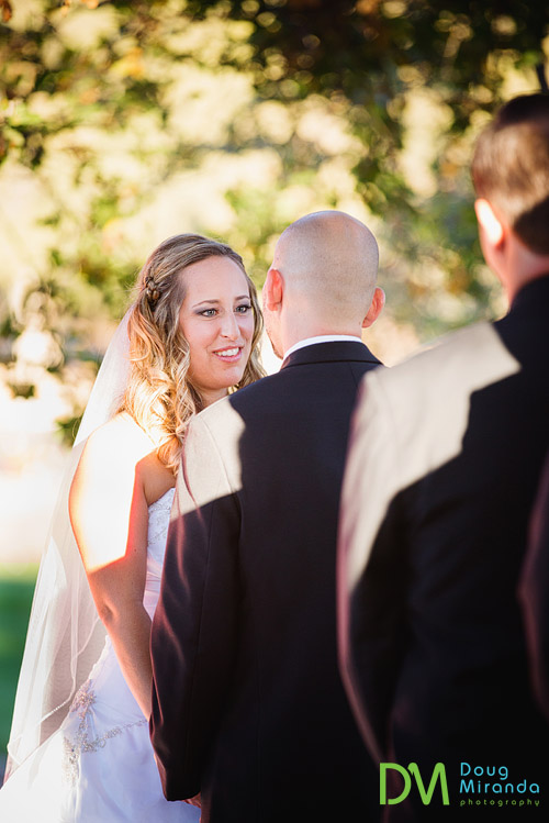 Jessica smiling at Alex during their wedding ceremony at the ridge in auburn