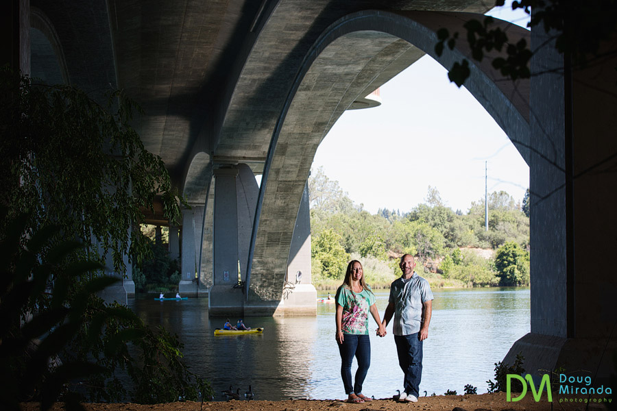 old folosm engagement photos of a couple holding hands under a bridge