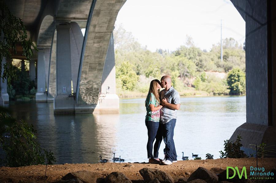 folosm engagement photos of a kissing couple under a bridge